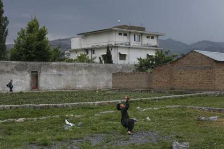 Resident boy Adeel, 8, plays with a tennis ball in front of the compound where U.S. Navy SEAL commandos reportedly killed al Qaeda leader Osama bin Laden in Abbottabad May 5, 2011. Pakistan, in apparent reference to old rival India, said on Thursday any country that tried to raid its territory in the way U.S. forces did to kill Osama bin Laden would face consequences from its military.  REUTERS/Akhtar Soomro (PAKISTAN - Tags: CRIME LAW MILITARY CIVIL UNREST POLITICS)   FOR BEST QUALITY IMAGE: ALSO SEE GM1E78I1N5A01. - RTR2M0YE